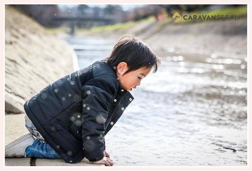 川原で水面を見つめる男の子