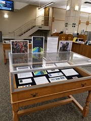 Wood and glass display case containing images of refugees and resources.