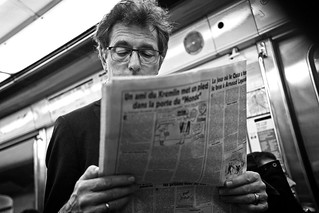 Reading a newspaper on the metro. | by Nicolas Winspeare