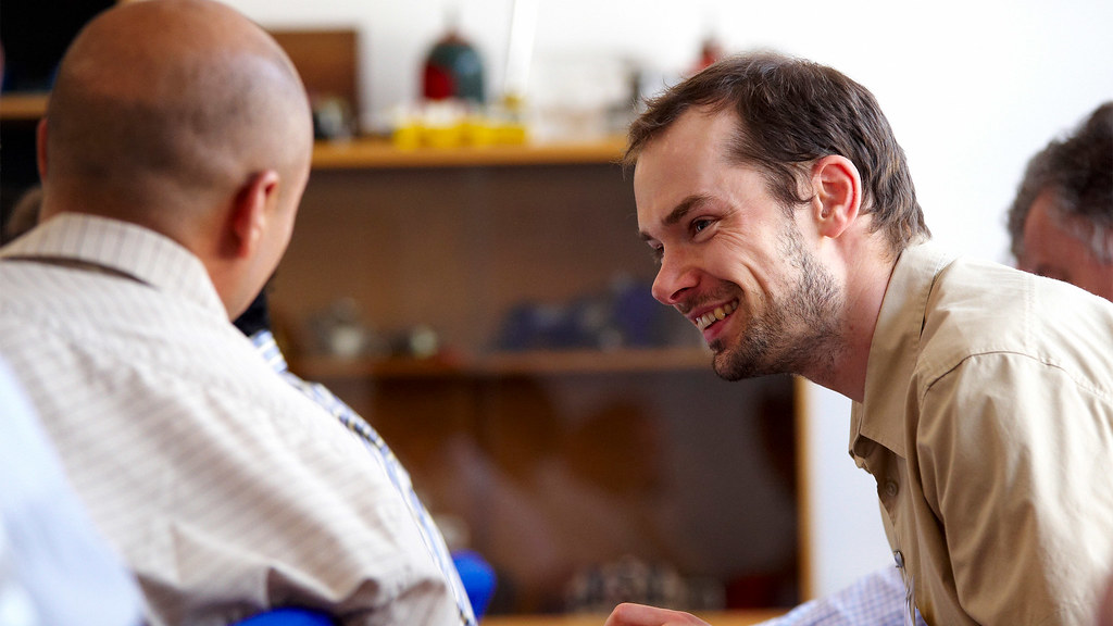 Close up of two men sat talking at conference