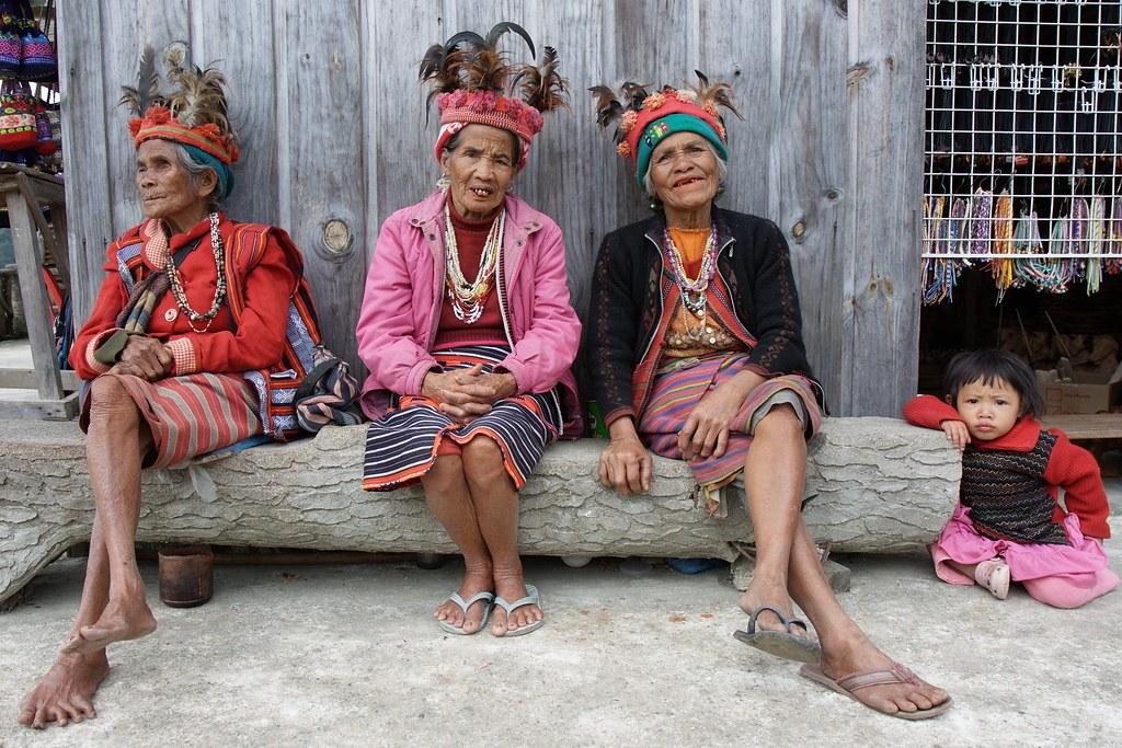 伊富高人穿著原住民服飾提供觀光客拍照,以此收費。圖片來源:Stefan Munder(CC BY 2.0)