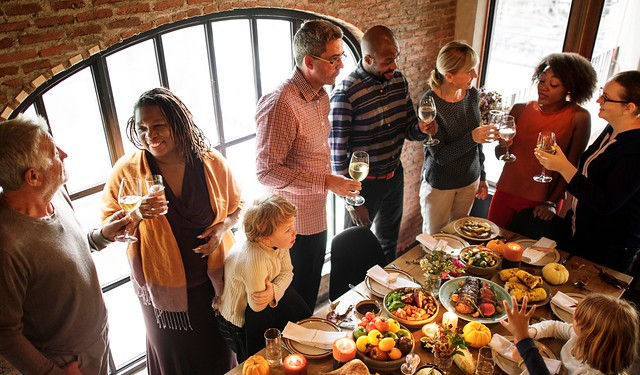 People gathering around Thanksgiving table