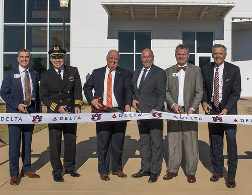 Officials with Auburn University and Delta Air Lines cut a ribbon in front of the new Delta Air Lines Aviation Education Building
