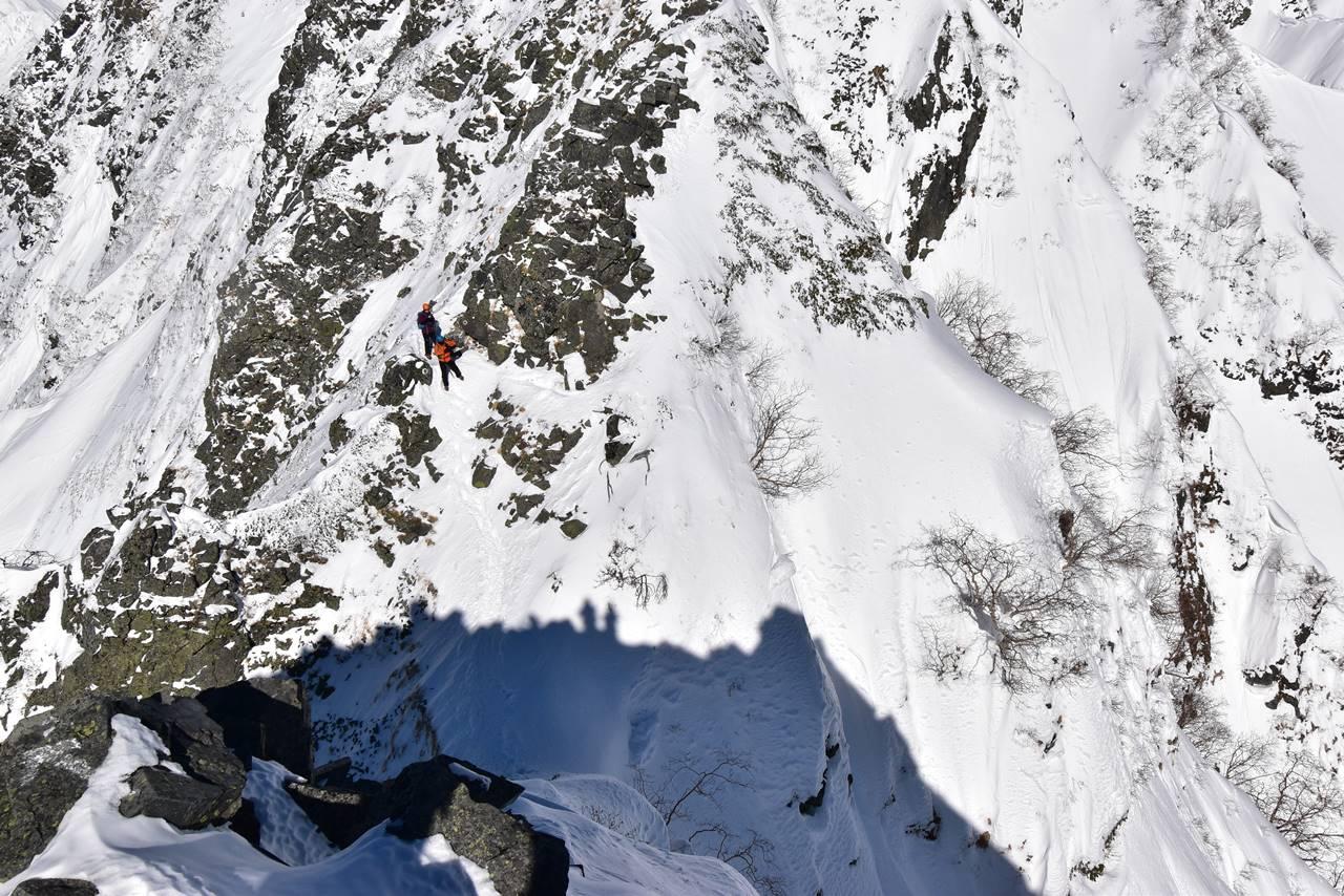 雪の西穂高岳稜線を歩く登山者