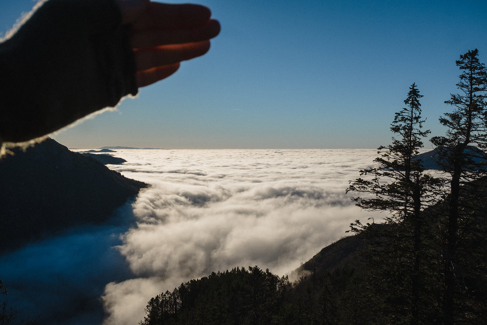 View from a mountain, fog fills the valley below. Hand shades the sun from shining directly into the camera.