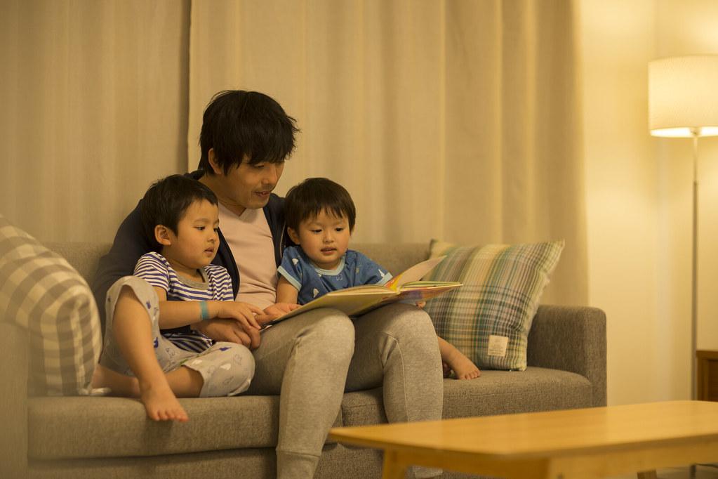 子ども達に絵本を読んで聞かせる家庭的なパパ