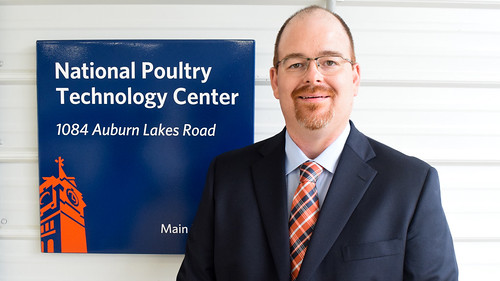 Jeremiah Davis stands next to sign that reads National Poultry Technology Center