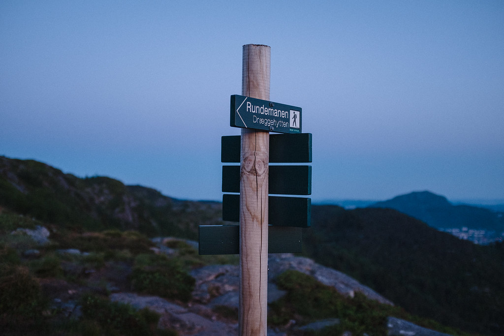 Signpost at dusk, mountain in the distance.