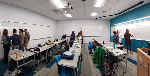 Photo of recently renovated classroom, where desks are ensconced in whiteboards. Students are working in small groups at each whiteboard - one at each wall - to draw the phylogeny from memory