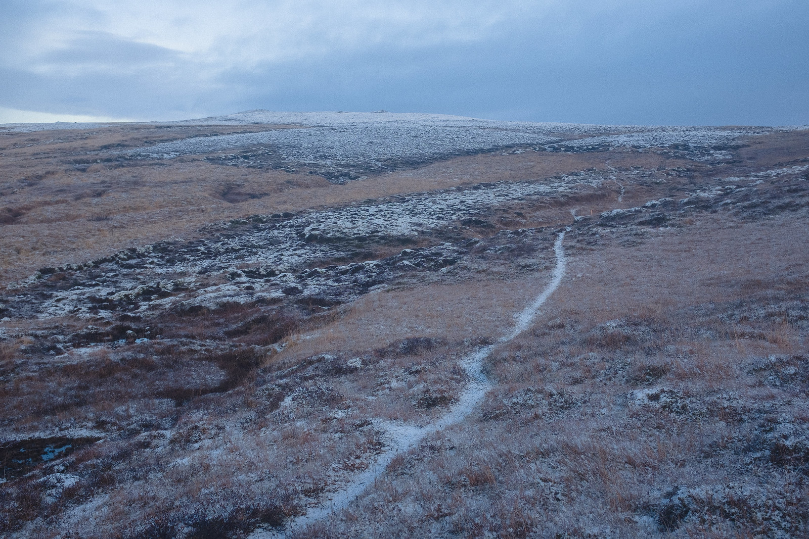 singletrack through moorland in autumn, thin layer of snow.