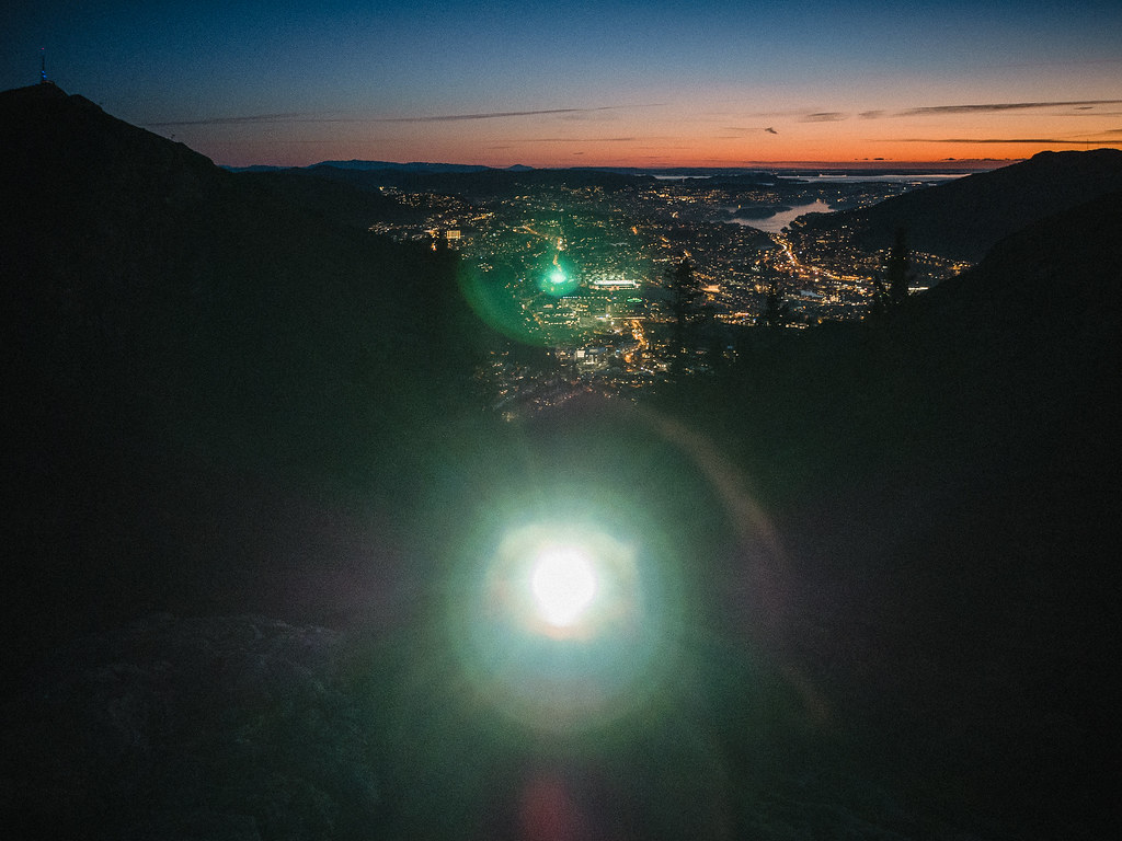 Upper half of a face, headlamp shining straight at the camera. Town at dusk in the background.
