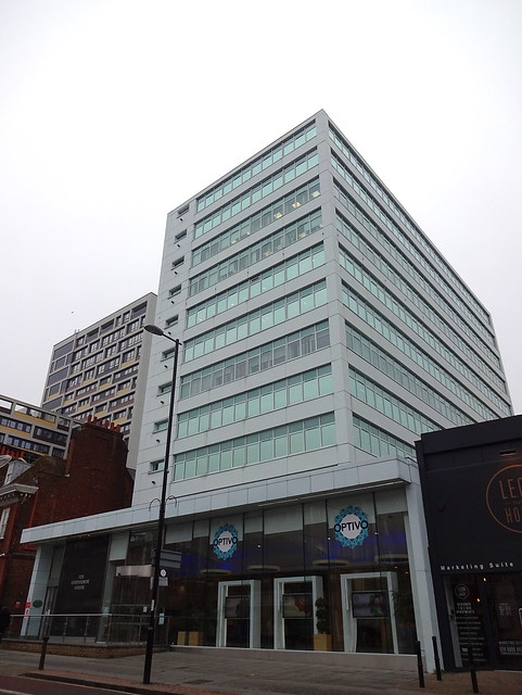 "A multi-storey office block with white cladding.  The ground floor is larger than the other floors, and bears the logo of a company called ""Optivo"".  Another office block of a similar height is visible beyond."