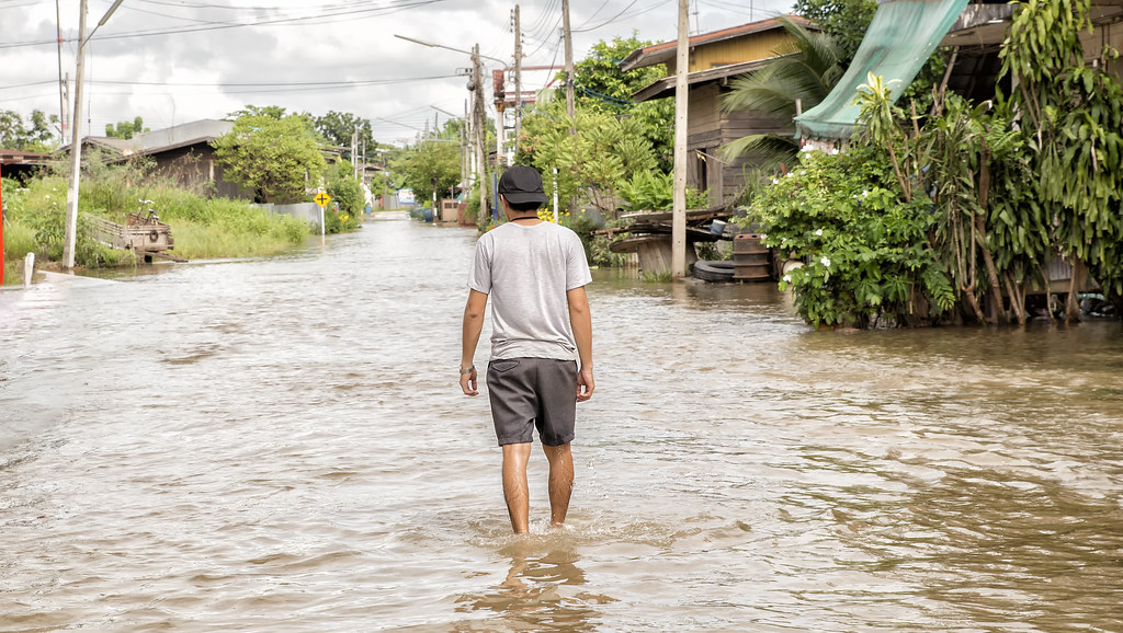 Man walking down flooded street.