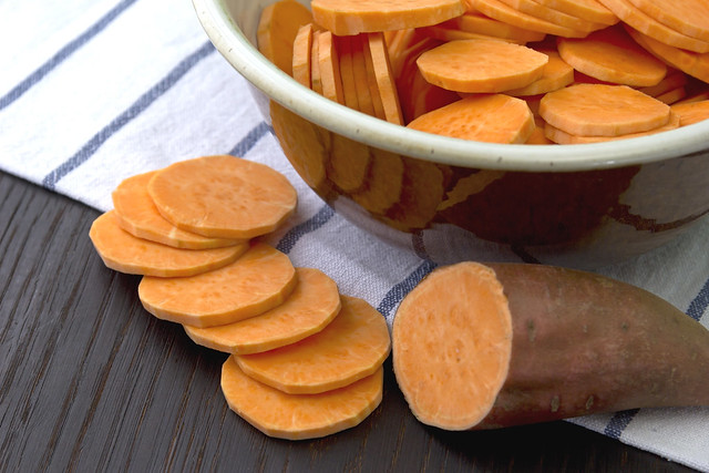 Sweet potato on wooden table and in the bowl