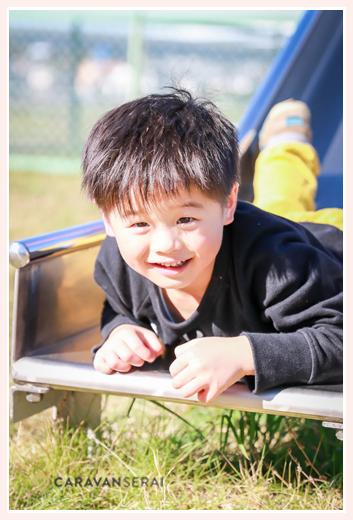 公園のすべり台で遊ぶ男の子