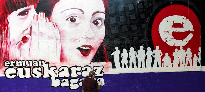 La foto muestra al autor pintando el mural de San Antonio