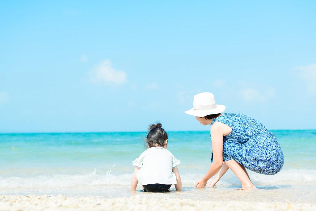 砂浜で一緒に遊ぶママと子ども