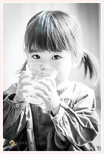 コップでお茶を飲む女の子 モノクロ