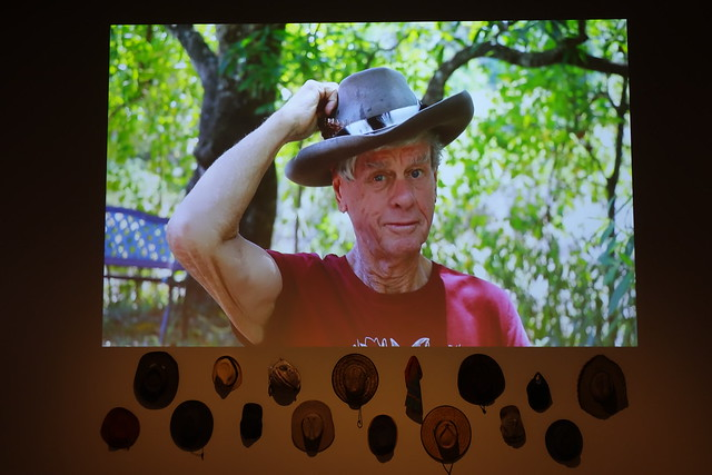 John Sweet dons his Akubra in our Hats of Mackay video work. His hat hangs below the video in amongst the fifteen other hats in this work.