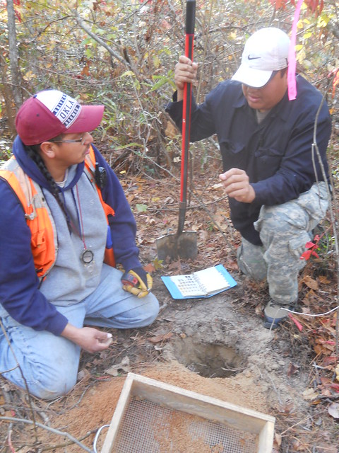 Tribal heritage paraprofessional instructs colleague on soil types during a survey