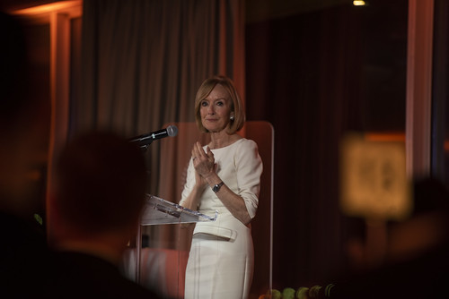 Judy Woodruff stands at a podium