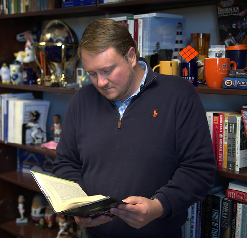 James Long reads a book in front of a bookcase