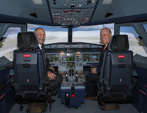 Steven Leath and Paul Jacobson sit in a flight simulator