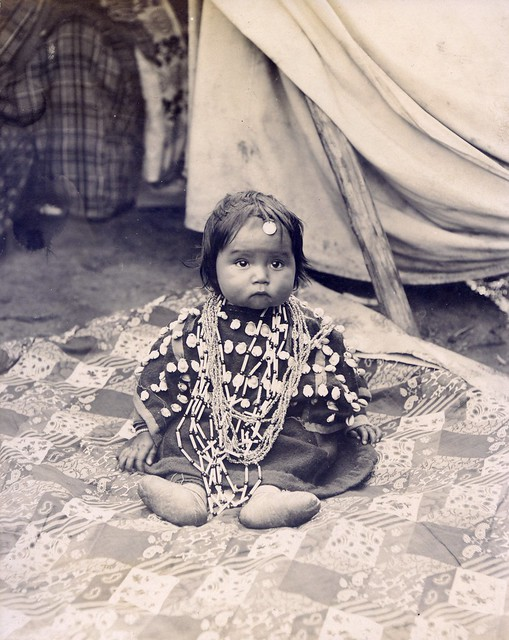 Cheyenne baby in dress with cowrie shells