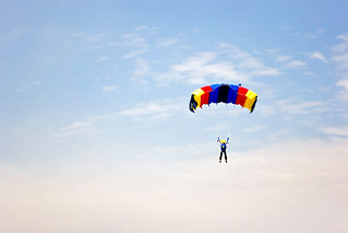 Red, yellow and blue parachute against cloudy sky | by Horia Varlan