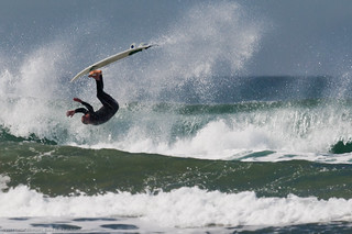 Surfer flipping on a top turn | by mikebaird