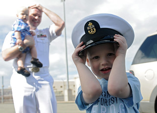 Boy wears his father's hat during USS Abraham Lincoln arrival. | by Official U.S. Navy Imagery