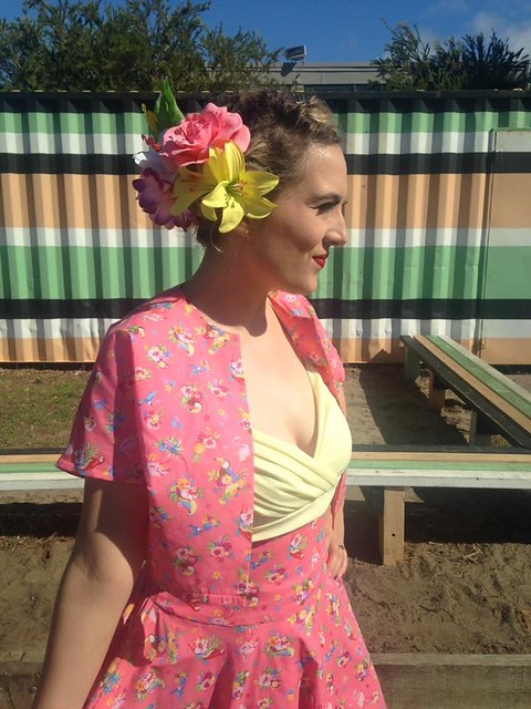 A woman wears a 50s-inspired shelf bust dress with matching floral headpiece and kimono sleeve jacket.