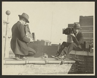 [Two photographers taking each others' picture with hand-held cameras while perched on a roof] (LOC) | by The Library of Congress