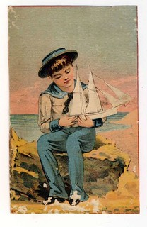 BOY SETTING ON ROCK HOLDING A BOAT | by oldsailro