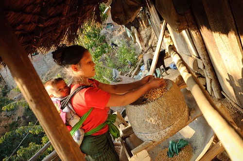 Lao Mom & Baby Feeding Corn into Grinder | by goingslowly