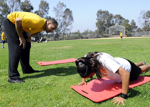 Sailor cheers a middle school student to finish her push-ups during a physical fitness field day at Jean Farb Middle School | by Official U.S. Navy Imagery