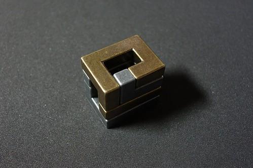 "HUZZLE_CAST COIL_(2016_10_01)_2_resized_1 ""Huzzle"" という知恵の輪的な立体パズルの写真。2個の金属製の角ばった複雑な立体形状が組み合わさっている。片方は黄金色でもう片方は銀色である。"