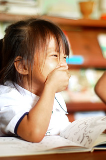 Laughing girl with picture book | by Chea Phal