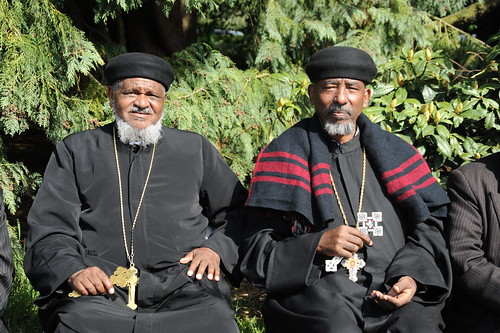 "Holding blessed Christian crosses, senior religious leaders in black and red garments, from north African country Eritrea (Punt, ""Ta Netjeru,"" meaning god's land), at the 20th year anniversary of Eritrea's independence, Volunteer Park, Seattle, Washington 