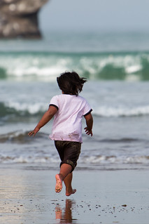 Child romps and jumps on the sand beach running into the ocean near Pillar Rock. | by mikebaird