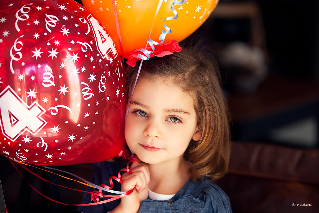 Happy Girl With 4 Year Old Birthday Balloons