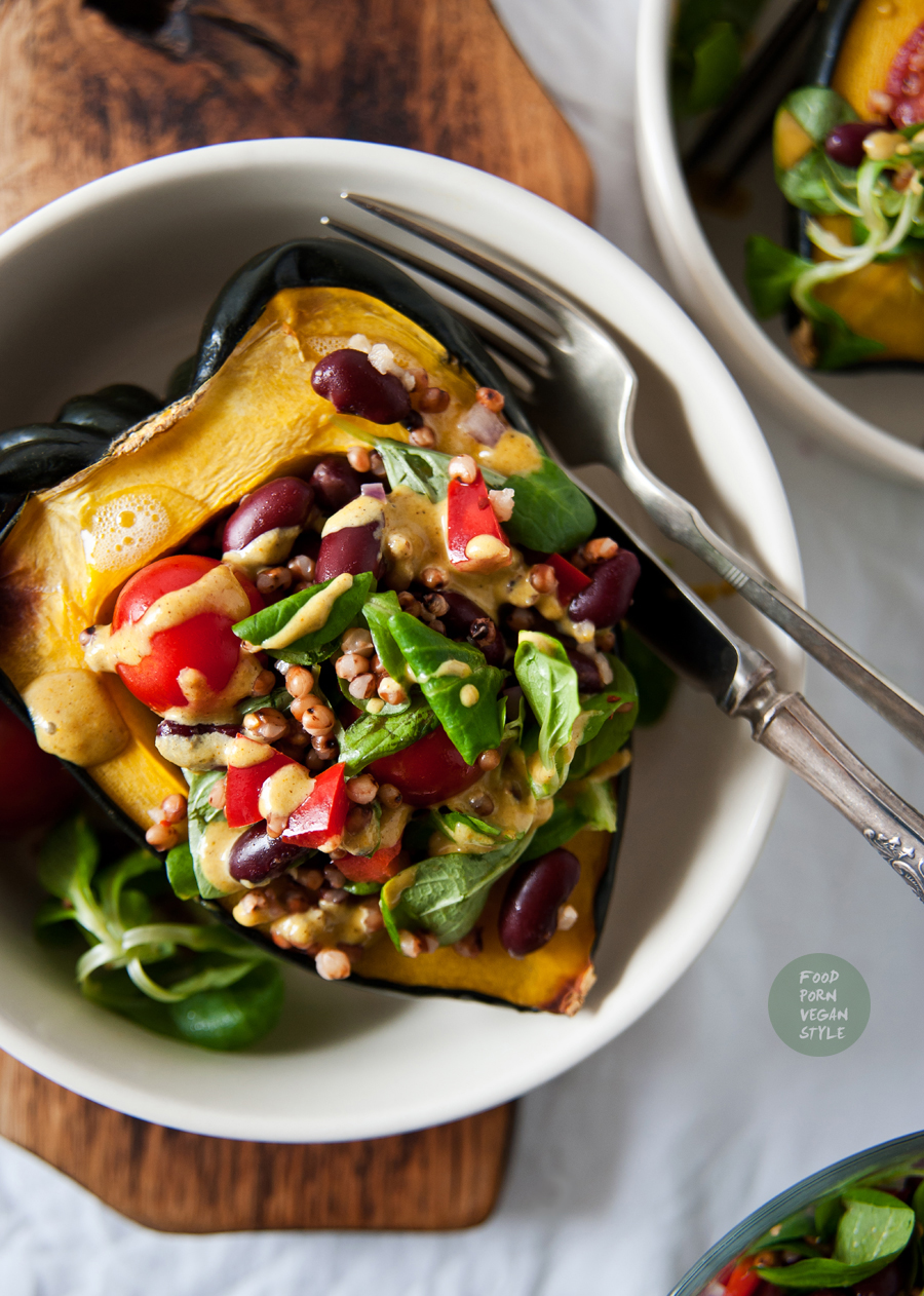 Roasted acorn squash stuffed with sorghum grains and vegetables, topped with an indian tahini sauce