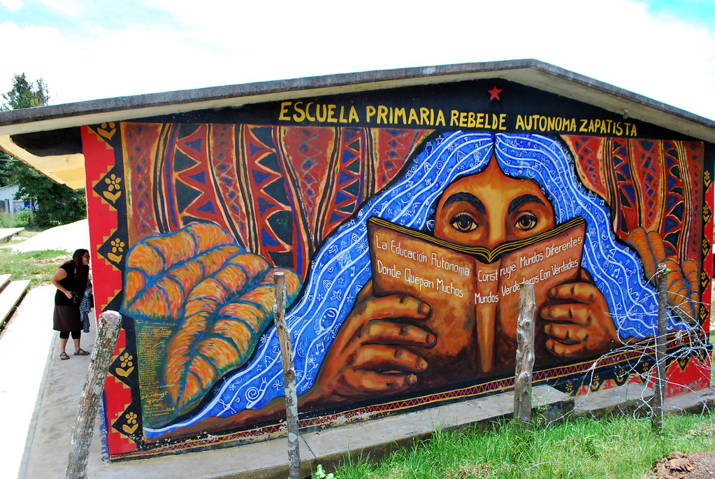 Mural on the side of a building, showing a person holding a book in front of their face; their eyes are visible over the book and look out at the viewer. Hair is blue like a river and filled with symbols. Behind the person is a forest of decorated tree trunks and tropical foliage. Above the person are the words