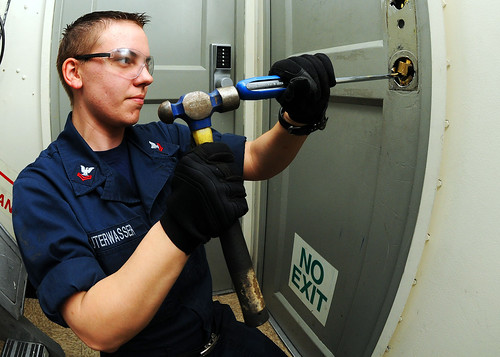 Saint Louis native/Sailor clears debris from door hole. | by Official U.S. Navy Imagery