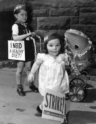 "Two young children push a dolls carriage and carry signs in support of their parents' strike.  Their signs read ""Strike!"" and ""I Need a Healthy Diet!"" 