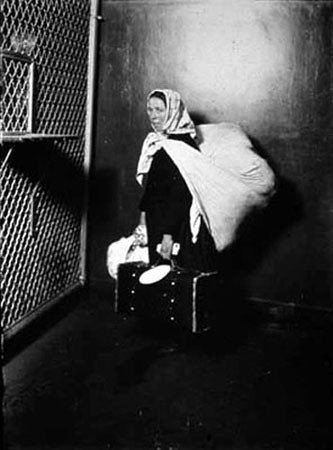 Ellis island lewis hine woman carrying all her possessions on her back ellis island