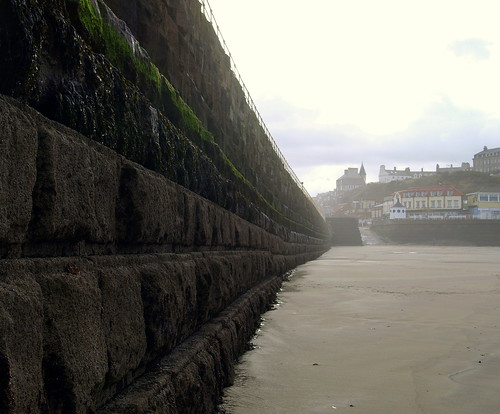 The towering pier/harbour rampart from the beach in Whitby | by Tony Worrall