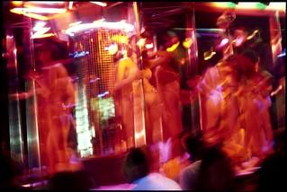 Prostitutes dance for prospective clients in a bar in the red-light district, Pat Pong, Bangkok, Thailand. | by axlright