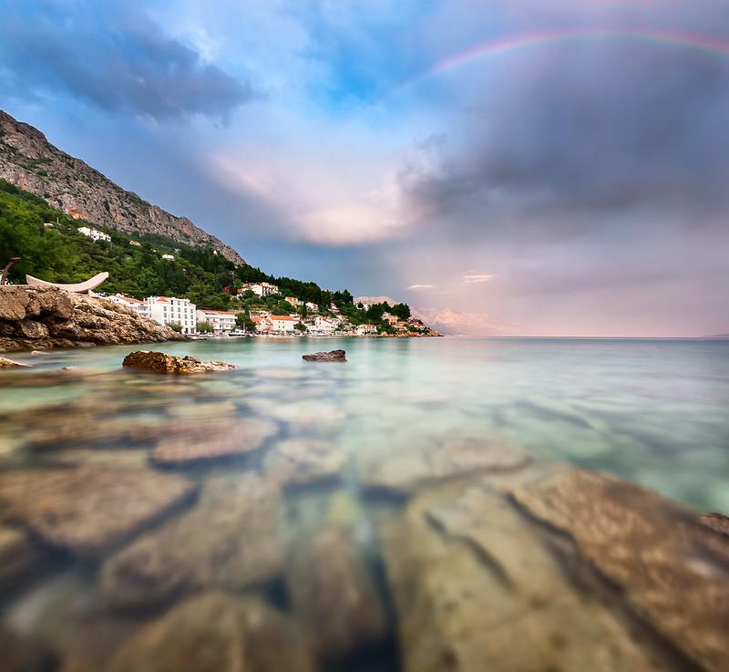 Rainbow Over Rocky Beach And Small Village After The Rain Dalmatia Croatia