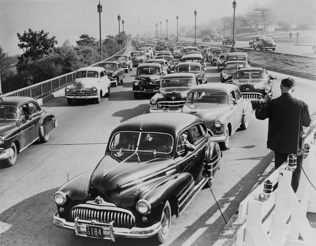 lots of rounded 1940s cars with split windshields and incredibly large chrome bumpers stuck in traffic